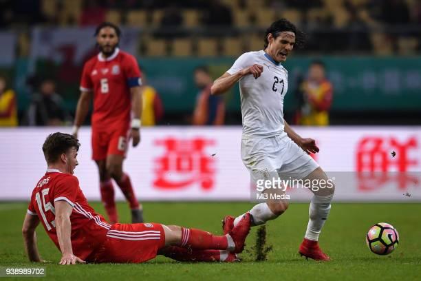 Edinson Cavani right of Uruguay national football team kicks the ball to make a pass against a player of Wales national football team in their final...