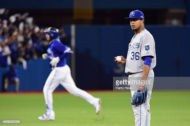 Edinson Volquez of the Kansas City Royals reacts as Chris Colabello of the Toronto Blue Jays runs the bases after hitting a solo home run in the...
