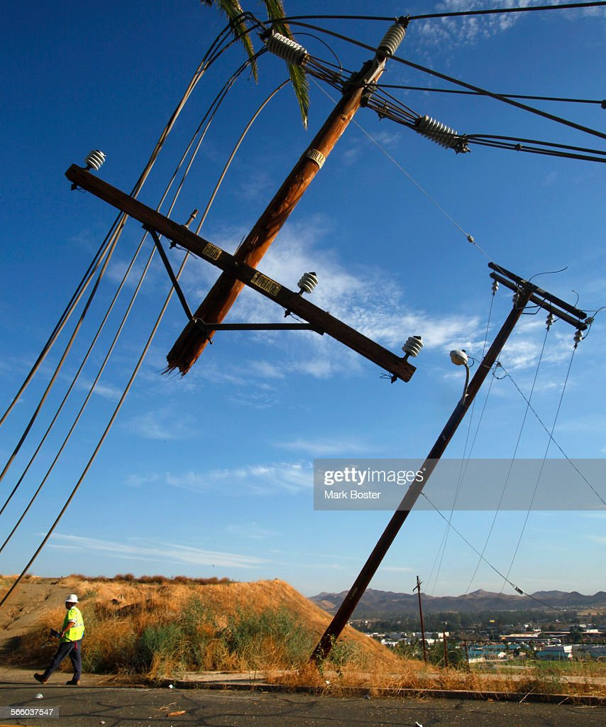 Edison crews work carefully around the downed power poles and broken ...