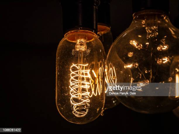 edison lightbulbs glowing against a black background - panyik-dale stock photos and pictures