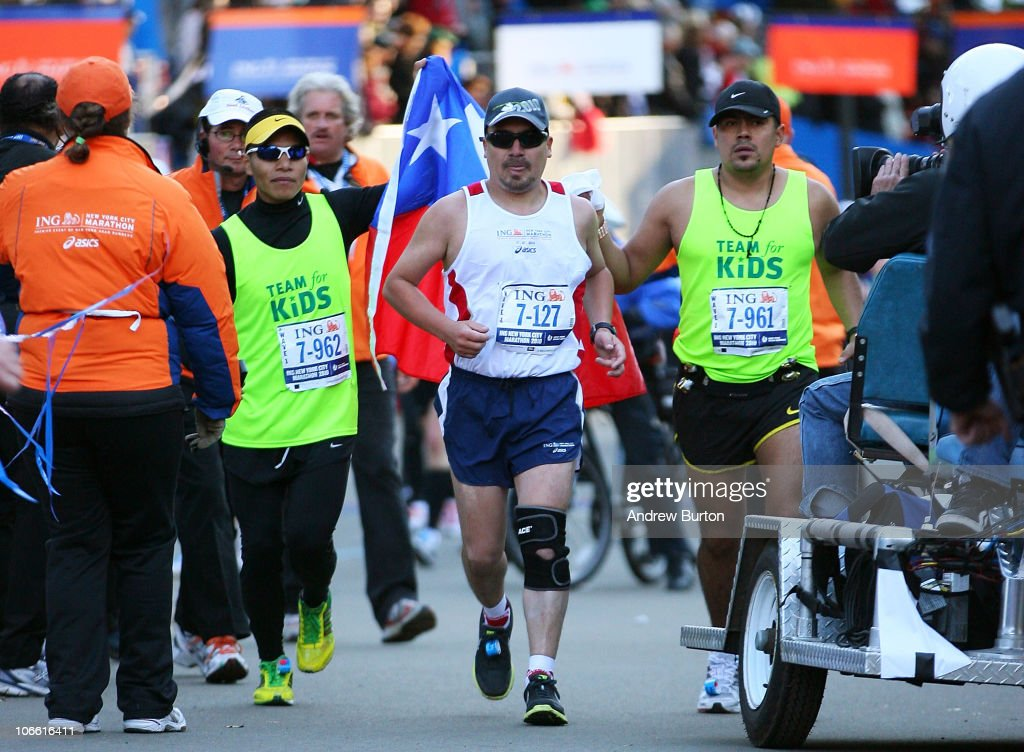 Edison Pena (C), one of the recently recued Chilean miners, approaches the finish line to complete the 41st ING New York City Marathon in Central Park on November 7, 2010 in New York City.