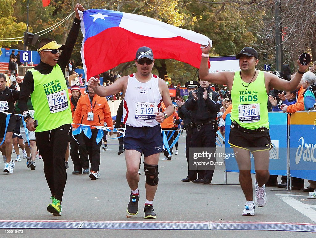 Edison Pena (C), one of the recently rescued Chilean miners, crosses the finish line to complete the 41st ING New York City Marathon in Central Park on November 7, 2010 in New York City.