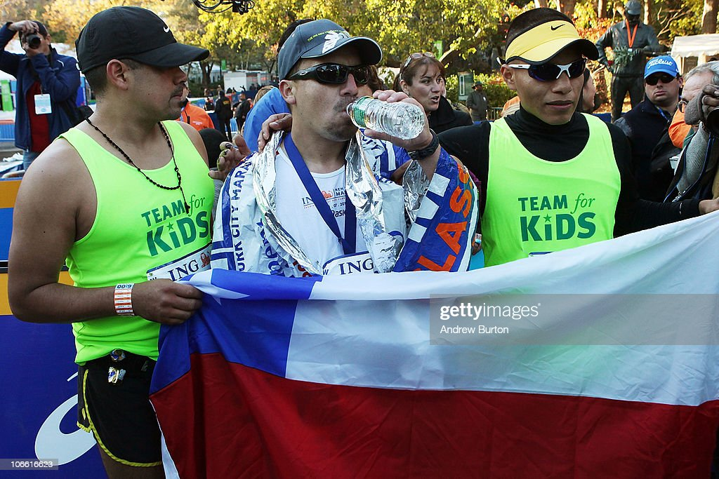 Edison Pena (C), one of the recently rescued Chilean miners,poses for photos after completing the 41st ING New York City Marathon in Central Park on November 7, 2010 in New York City.