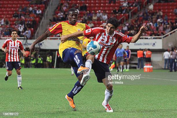 Edison Toloza of Morelia struggles for the ball with Jonny Magallon of Chivas during a match between Chivas v Morelia as part of the Clausura 2012 at...
