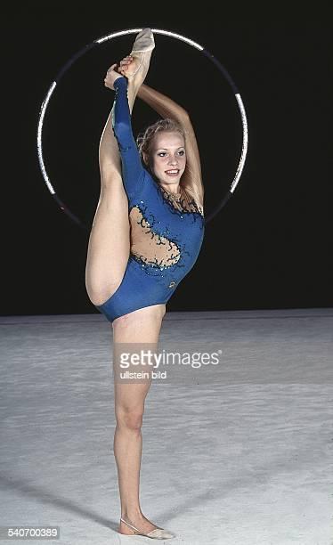 Edita Schaufler Rhythmische Sportgymnastik hält während einer Übung mit dem Reifen ihr senkrecht hochgestrecktes Bein mit beiden Armen hinter dem...