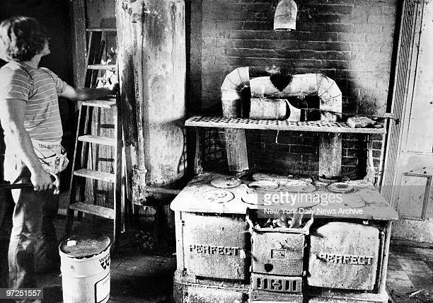 Edith Bouvier Beale house in East Hampton LI Young worker seems impressed by antique stove and hot water tank in the main kitchen