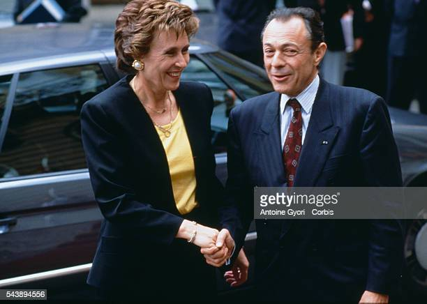 Edith Cresson the first woman Prime Minister of France shakes hands with outgoing Prime Minister Michel Rocard