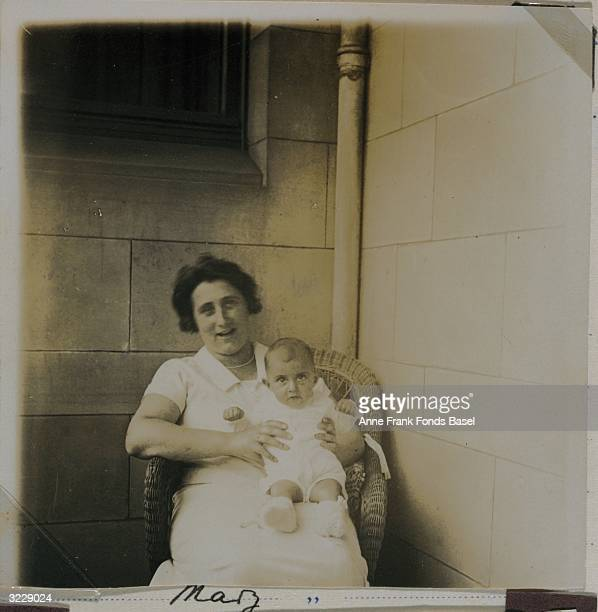 Edith Frank the mother of Anne Frank sits in a wicker chair holding her infant daughter Margot on the balcony of her home Frankfurt am Main Germany...