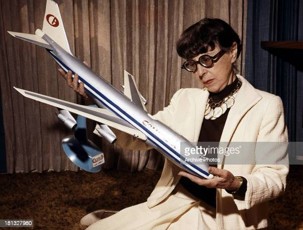 Edith Head examines a model airplane on set of the film 'Airport' 1970