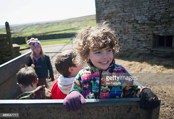 Edith Owen rides in a trailer towed behind a quad bike at Ravenseat, the farm of the Yorkshire Shepherdess Amanda Owen on April 15, 2014 near Kirkby...