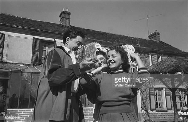Edith Piaf And Jacques Pills Edith PIAF et Jacques PILLS en compagnie d'une femme en costume traditionnel régional la chanteuse essayant une coiffe