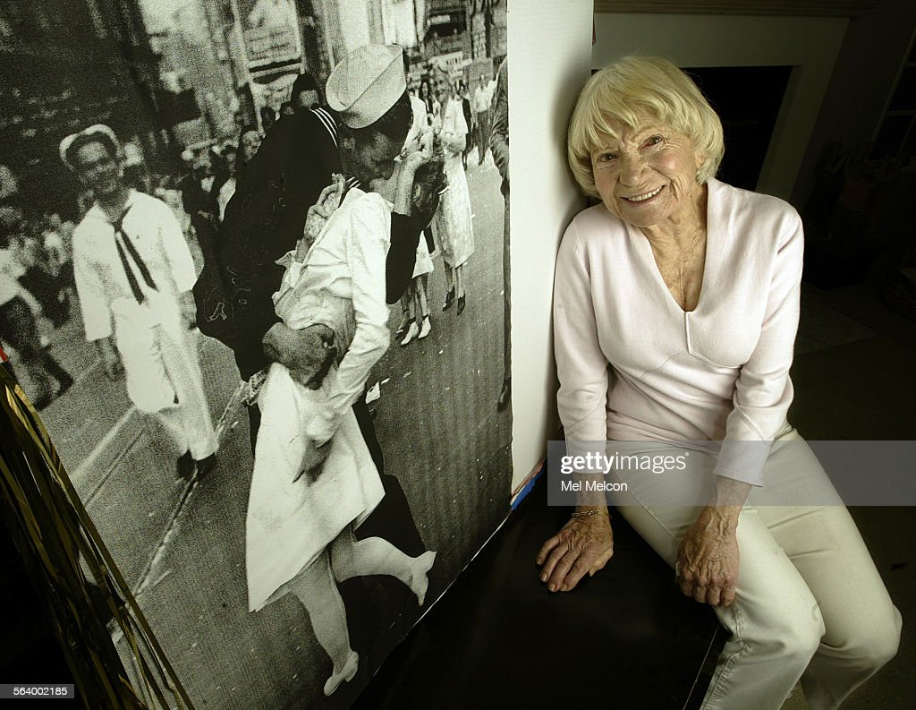 Edith Shain sits next to an enlarged photograph of her being kissed by a sailor in Times Square on : News Photo