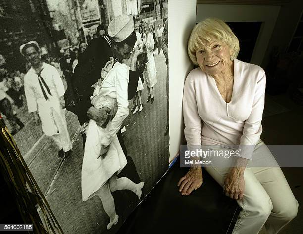Edith Shain sits next to an enlarged photograph of her being kissed by a sailor in Times Square on VJ day, August 15 celebrating the end of World War...