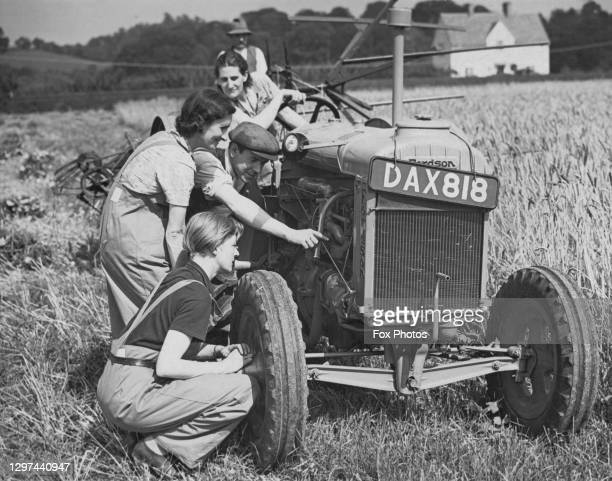 Edith Smith, Lillian Jarvis and Mrs F Holmes, members of the Women's Land Army receive instructions on operating a Standard Fordson tractor on 15th...