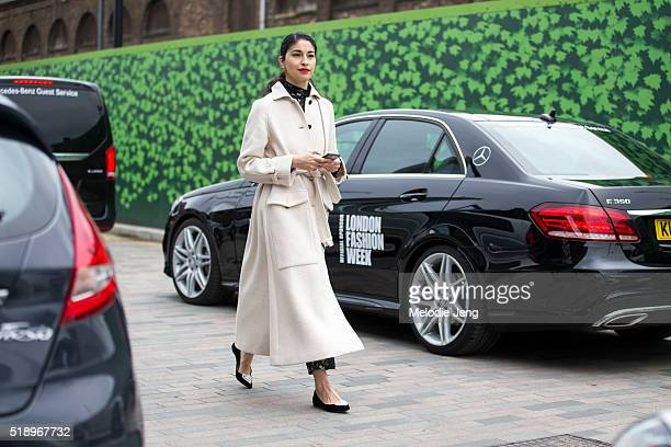 Editor and Designer Caroline Issa wears a long white belted coat and black flats with silver hearts at the Mary Katrantzou show at 1 Granary Square...