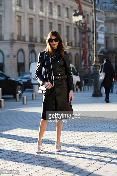 Editor Ece Sukan wears a Comme des Garcons leather jacketdress and Prada silver meallic heels at the Schiaparelli show at Place Vendome on January 25...