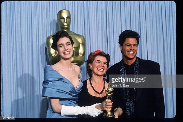 """Editor Gabriella Cristiani holds her Best Film Editing Oscar for """"The Last Emperor"""" while standing next to actor Rob Lowe and actress Sean Young at..."""