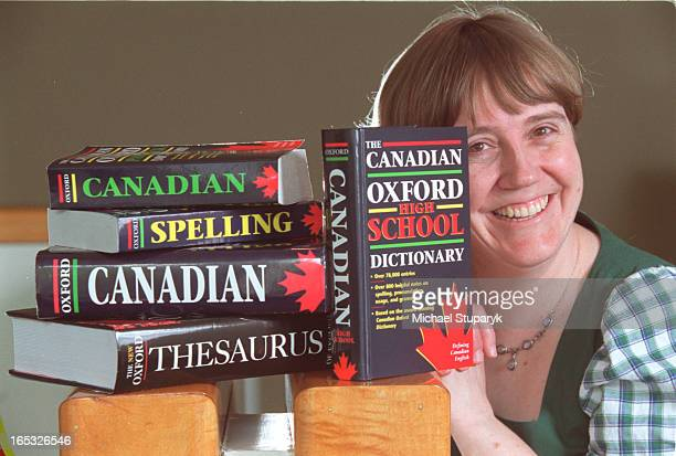 Editor in chief of Canadian Oxford Dictionary Katherine Barber with a stack of dictionaries