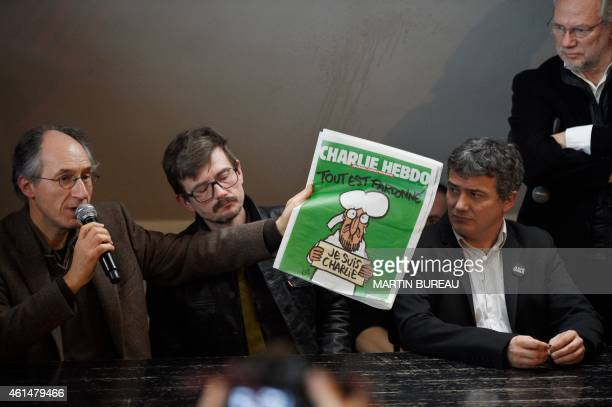 Editor in chief of French satirical weekly Charlie Hebdo Gerard Briard holds up the new issue of the French satirical weekly Charlie Hebdo flanked by...