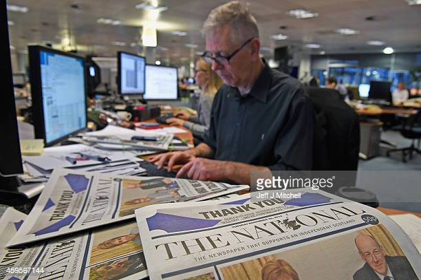 Editor Richard Walker sits at his computer near copies of 'The National' as staff work in the newsroom after its yesterday's launch on November 25...