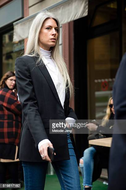 Editor Sarah Harris wears a black blazer over a white shirt and top over blue jeans outside the Sportmax show during the Milan Fashion Week...
