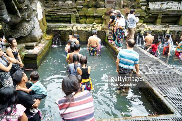 editorial use: group of  wet balinese hindu men and women waiting for ritual purification in the holy spring at tirta empul temple, bali - pura tirta empul temple stock pictures, royalty-free photos & images