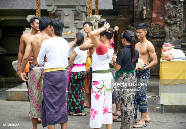 editorial use: group of young balinese hindu men and women preparing for ritual purification at tirta empul temple, bali - pura tirta empul temple stock pictures, royalty-free photos & images