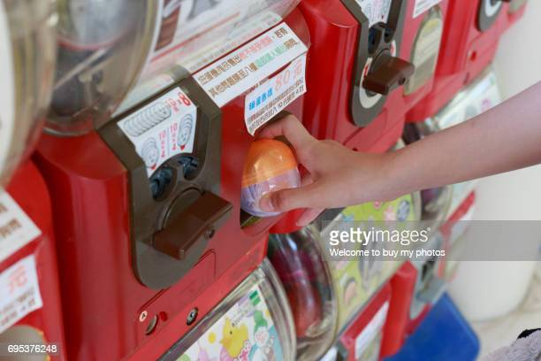 Editorial use only : Girls flipping coins and taking out a Capsule Toy (Japanese: Gashapon) from vending machine.