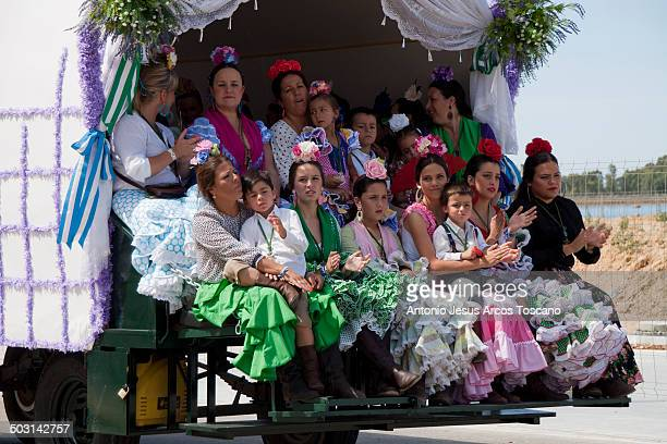 CONTENT] Editorial Use Only Group of pilgrims dressed in clothing typical flamenco sitting and singing in the wagon decorated for the output of the...