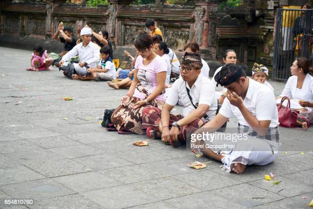editorial use: tourist and balinese hindu men and women praying at tirta empul temple, bali - pura tirta empul temple stock pictures, royalty-free photos & images