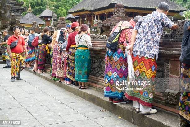 editorial use: tourist and balinese hindu men and women wearing colourful sarongs visiting tirta empul temple, bali - pura tirta empul temple stock pictures, royalty-free photos & images