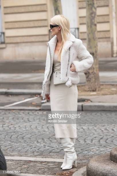 Editorialist Kate Davidson Hudson wears a Fendi sling bag, Pologeorgis jacket with a white pencil skirt and white knee high boots on March 02, 2019...