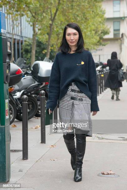 EditorinChief at InStyle China Jerri Ng wears a Celine sweater Sacai skirt Stuart Weitzman boots and Loewe brooch day 3 of Paris Womens Fashion Week...
