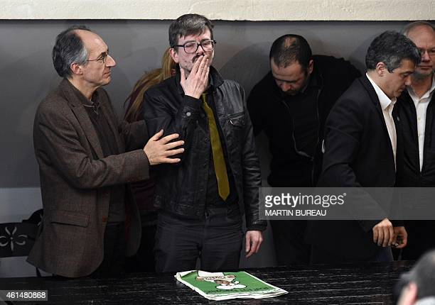 Editorinchief of French satirical weekly Charlie Hebdo Gerard Briard looks on as French cartoonist Renald Luzier aka Luz blows a kiss after holding a...