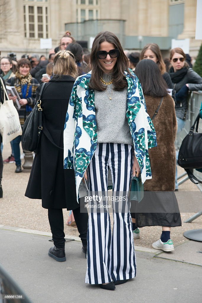 Editor-in-chief of Vogue Mexico and Latin America Kelly Talamas wears a Polite coat, Chanel sunglasses, Mixed trousers, Vince top, Emporio Armarni shoes and Hunting season bag on day 7 of Paris Collections: Women on March 09, 2015 in Paris, France.
