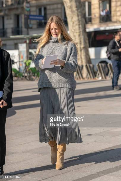 Editor-in-Chief Vogue.fr Jennifer Neyt wears a grey jumper and grey pleated skirt with camel boots on February 27, 2019 in Paris, France.