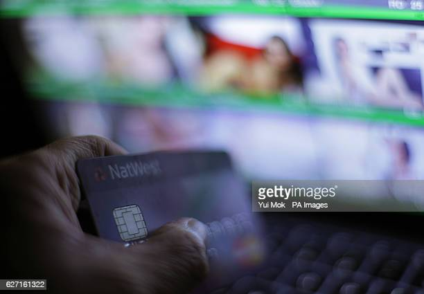 *Editors Note Content* A laptop user holding a bank card whilst browsing a porn site of 'webcam girls' on screen in London