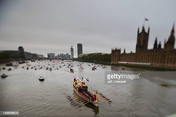 Editors Note Image was created using variable planed lens. The royal rowboat Gloriana passes by the Houses of Parliament during the Diamond Jubilee...