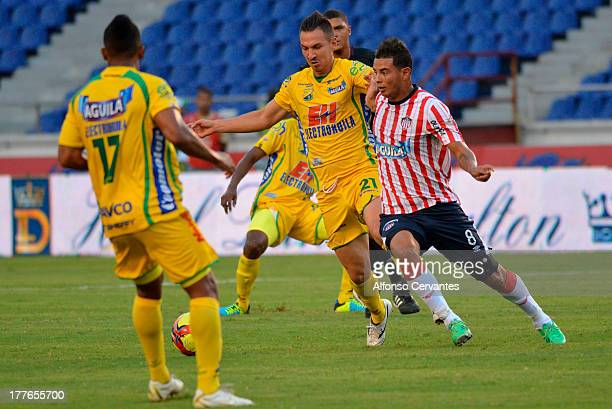 Ediwin Cardona of Junior fights for the ball with Cesar Hinestroza of Huila during a match between Junior and Atletico Huila as part of the Liga...