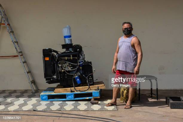 Edmario Costa, a bakery owner, poses for a photo next to a power generator during a blackout due to fire in the Macapa substation on November 8, 2020...