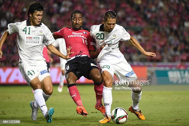 Edmilson of Cerezo Osaka and Tsubasa Aoki Naoya Okane of FC Gifu compete for the ball during the JLeague second division match between Cerezo Osaka...
