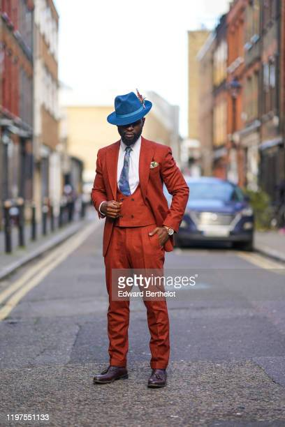 Edmond Kamara wears a blue hat with a feather a white shirt a blue tie an orange blazer jacket orange pants purple leather shoes a watch during...