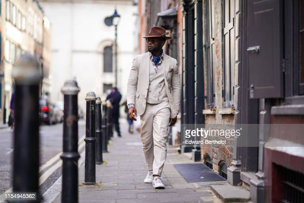 Edmond Kamara wears a hat a white three pieces suit a scarf white blazer jacket white pants white sneakers shoes sunglasses during London Fashion...