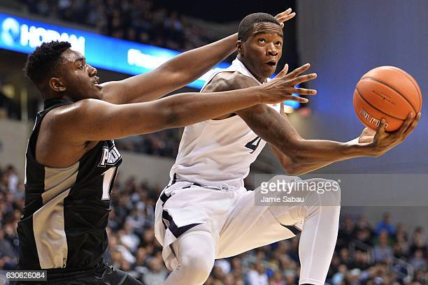 Edmond Sumner of the Xavier Musketeers lays in for two points while being fouled by Kalif Young of the Providence Friars in the second half on...