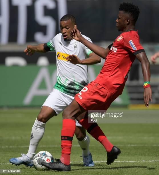 Edmond Tapsoba of Bayer 04 Leverkusen is challenged by Alassane Plea of Borussia Moenchengladbach during the Bundesliga match between Borussia...