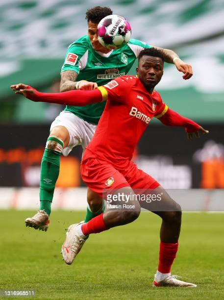 Edmond Tapsoba of Bayer Leverkusen battles for possession with Davie Selke of Werder Bremen during the Bundesliga match between SV Werder Bremen and...