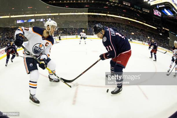 Edmonton Oilers center Connor McDavid and Columbus Blue Jackets left wing Matt Calvert battle for the puck during the third period in a game between...