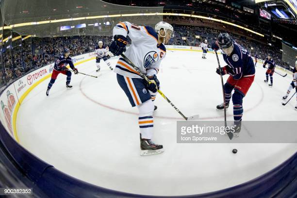 Edmonton Oilers center Connor McDavid and Columbus Blue Jackets left wing Matt Calvert battle for the puck during a game between the Columbus Blue...