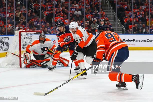 Edmonton Oilers Center Connor McDavid and Edmonton Oilers Right Wing Alex Chiasson battle Philadelphia Flyers Defenceman Andrew MacDonald infant of...
