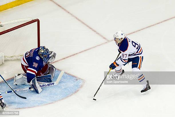 Edmonton Oilers Center Connor McDavid works the puck towards New York Rangers Goalie Henrik Lundqvist during the second period of a regular season...